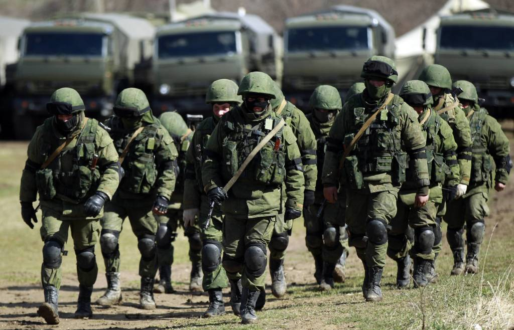 Armed men, believed to be Russians, march at their camp near the Ukrainian military base in Perevalnoye